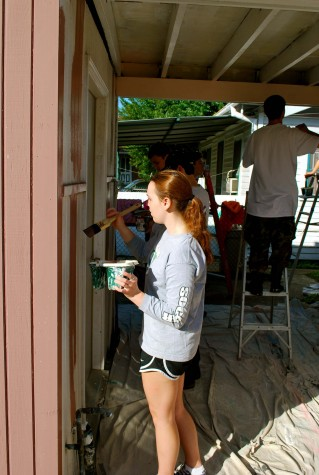 Junior Dakota Chamberlin paints the side of a house damaged by Hurricane Katrina. Students scraped and caulked the house the day before in preparation for painting. Photo: Ray O'Connor