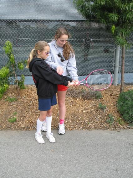 Anjali Shrestha | the broadview.  Delancie teaches Audrey Bjorklund how to properly hold and swing a racket at an after school tennis session. Bjorklund is one of 12 girls that she teaches after school tennis to.