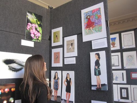Freshman Margaux Gaede checks out art by Convent seniors displayeed in the Four School art show. The annual show appears in the Main Hall for over a week. Anjali Shrestha | the broadview.