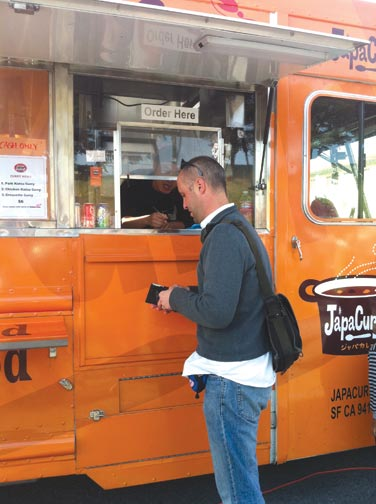 A customer at Fort Mason's weekly Off the Grid market pays for his order at JapaCurry, a food truck offering Japanese style curry rice. Over 30 trucks and tents are available at Fort Mason every Friday from 5 p.m.–10 p.m. KATY HALLOWELL | the broadview