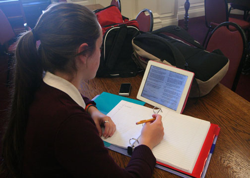 Sophomore Tess Holland studies math by collabrating her iPad and textbook. Freshman and sophomores were given smart covers are able to fold into stands, holding it up for horizontal viewing.