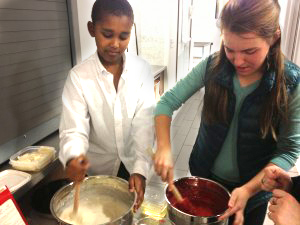 Senior Mary Katherine Michiels-Kibler and fifth grader Nahom Tesfaye mix cupcake batter. Cakes for a Cause held its first meeting today, after which members drove the desserts down to the Hamilton Family Center.