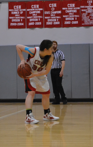 Senior guard Gina Domergue prepares to pass the ball to one of her teammates during a recent game. Domergue is wearing kinesiology tape on her right shoulder due to a tear in her labrum.
