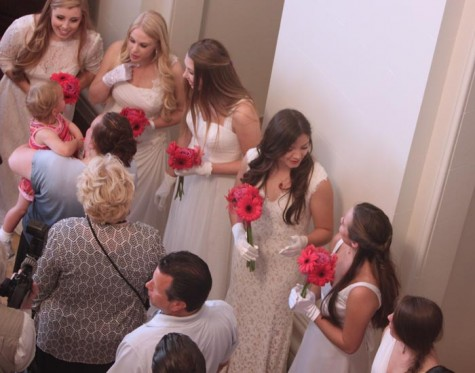 Seniors holding fuchsia gerberas greet their guests. The Class of 2014 greeted approximately 450 guests in a receiving line during Senior Tea this afternoon.