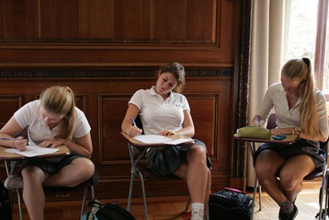 Seniors Sarah Niehaus, Christina Berardi, and Alex Wood (left to right) take notes during a  seminar style senior theology class.