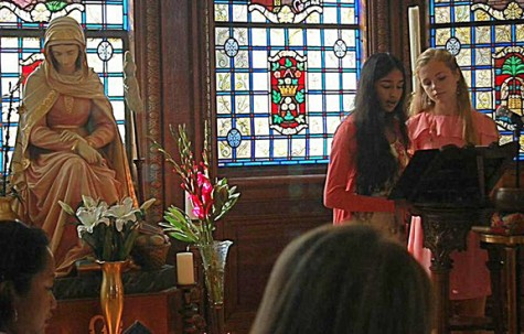 Freshmen Asha Khanna and Lily Niehaus open yesterday's prayer service for the Feast of Mater Admirabilis with the Call to Prayer. The statue is a likeness of the fresco in Rome, painted in 1844 by Pauline Perdrau.