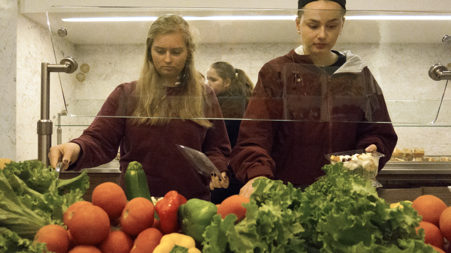 Juniors Anneka Dorresteyn and Katherine Burkett customize their salads from the salad bar.