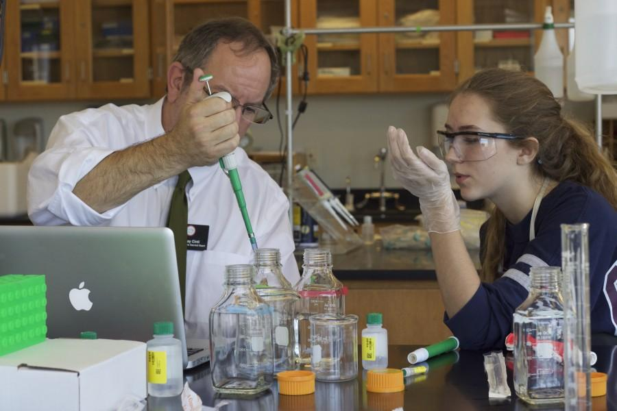 Senior+Madison+Stetter+examines+Conservation+Biology+teacher+Ray+Cinti%27s+experimental+demonstration.+The+experiments+themselves+are+conducted+by+the+student+independently+with+the+assistance+of+Cinti.