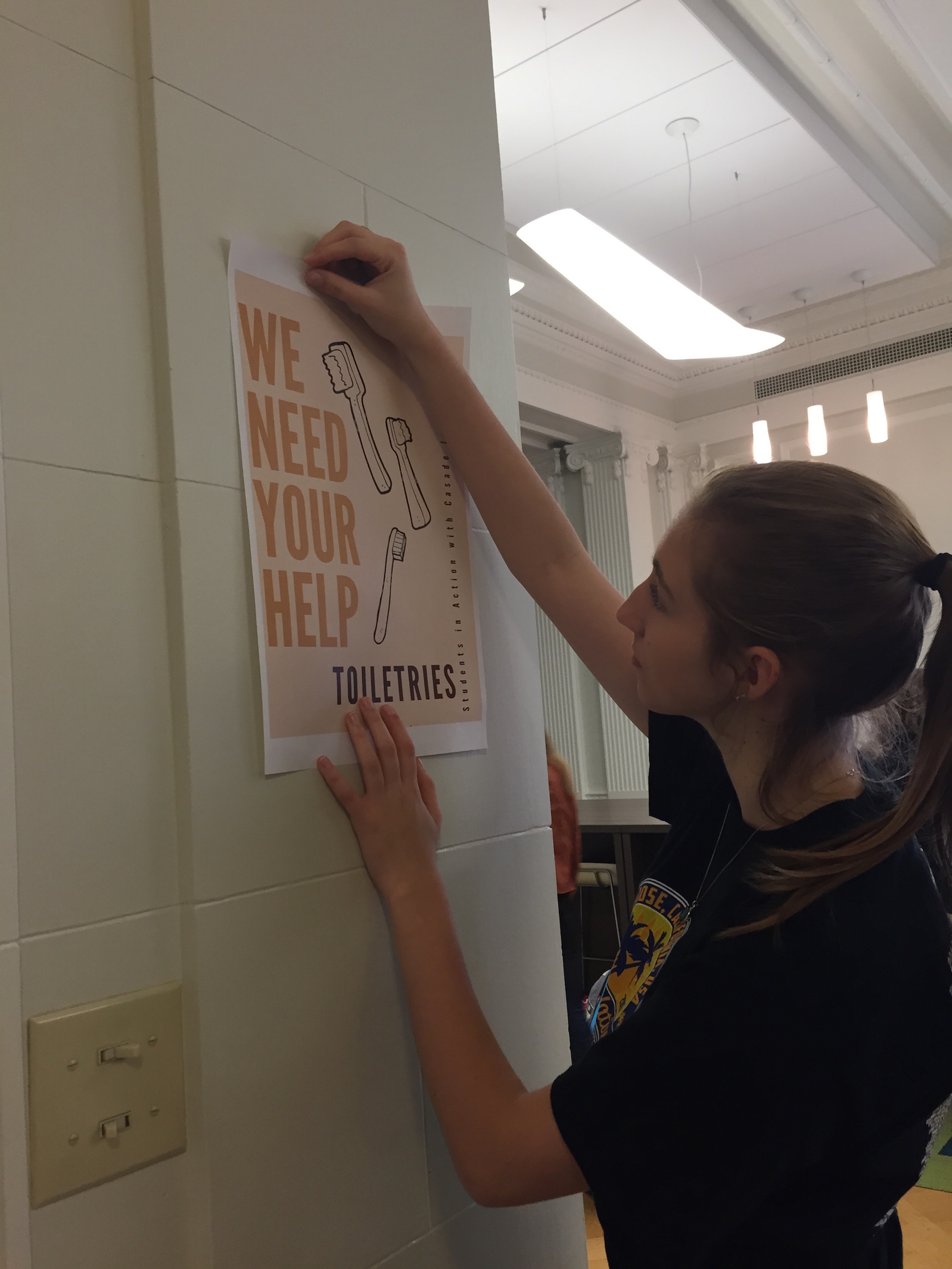 Senior Catherine Heinen tapes a promotional poster for the toiletry drive. Boxes are located in the library, gallery conference room and den.