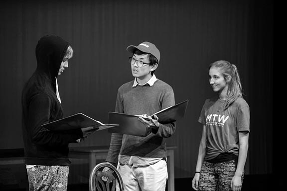 "Seniors Duncan McDonell, Daniel Im and Catherine Heinen (from left) read their lines during a rehearsal for the school production of  ""The Tempest"". The set features intricately designed lighting schemes and complex projections to add to the play's aura of mystery and magic."
