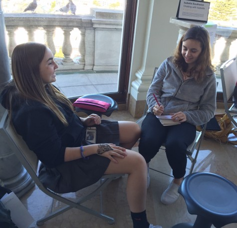 Freshman Megan Mullins  talks to junior Isabella Southwick at Southwick's booth. The booth allowed participants to discuss a topic of their choice and Southwick provides a drawing.
