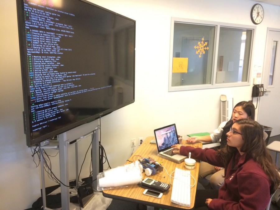 Sophomores+Halie+Kim+and+Carlota+Rubio+analyze+code+developed+for+their+self+made+cars.