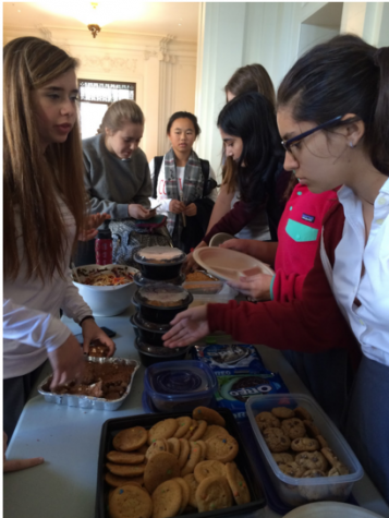 Sophomore Student Council President Carlota Rubio and Secretary Asha Khanna sell potluck dishes during today's lunch. Student Council organized the event, and sophomores were invited to bring in food.