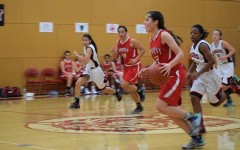 Junior Alyssa Alvarez dribbles the ball across the court during the last game of the Marin Academy Invitational Tournament. The team will play in a breast cancer awareness charity tournament beginning today.
