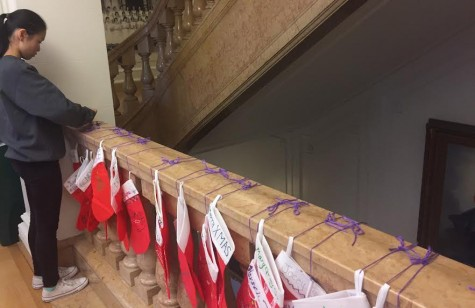Sophomore Activities Director Jilan Powers ties secret santa stockings to the marble stairs after school today. Students were advised to not spend over $5 per gift, although are allowed to if they choose.