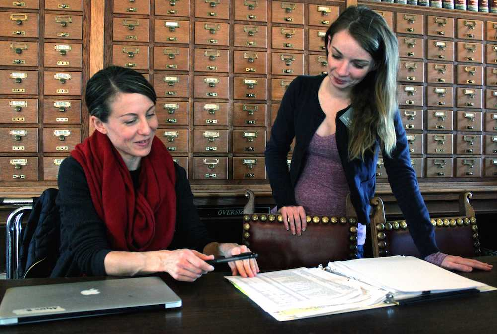 Newly-hired librarians Alyson Barrett-Ryan (left) Reba Sell are beginning the digitization process of the school archives as part of their library duties.