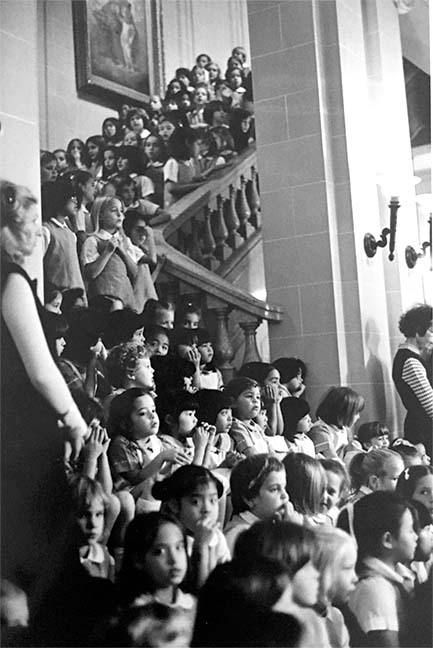 Elementary school students sit on the Marble Stairs as part of the 1977 Noëls celebration. Students wore white dresses for the occasion, unlike the dress uniform students wear today.