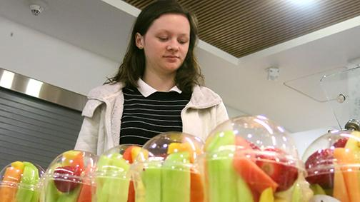 Senior Jennifer Quillen picks out a fruit cup from the cafeteria. Fruit is an essential part of a healthy breakfast but should be accompanied by protein and grains. the old saying
