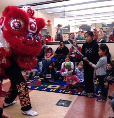 Two girls feed cabbage to a lion dancer from the Jing Mo Athletic Association during a performance at the Glen Park Public Library. The martial arts group performs lion dances at the library annually.