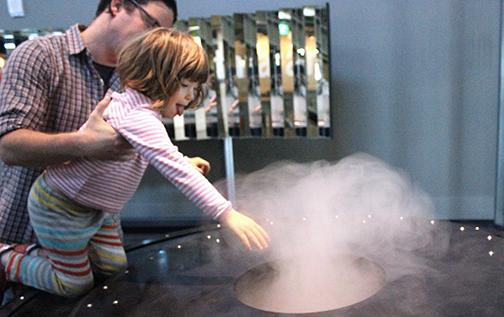 A father-daughter duo at the Exploratorium inspects a steam machine that functions as a study on atmosphere in the front gallery.
