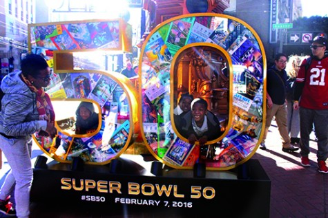 Football fans pose in front of Super Bowl installation at Pacific Avenue and Kearny Street. City officials working for the Super Bowl City stand at these installations and take photos for fans.