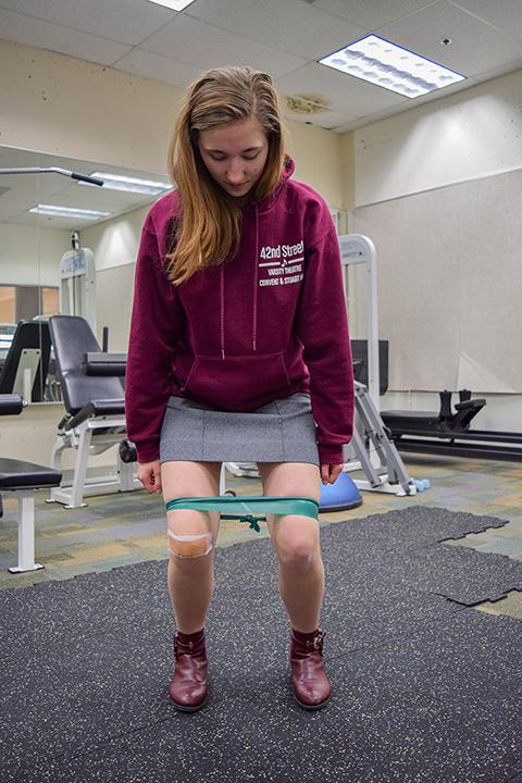 Senior Cat Heinen squats with a stretch band in order to help re-align her knees from patellofemoral syndrome, knee pain caused by outer leg muscles pulling the kneecaps the wrong way. Heinen performs a set of exercises and stretches every day including squats and leg extensions.