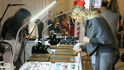 A woman inspects a necklace at a boutique during the Christmas on Broadway fundraiser. Local vendors donate a portion of their proceeds to the Schools.