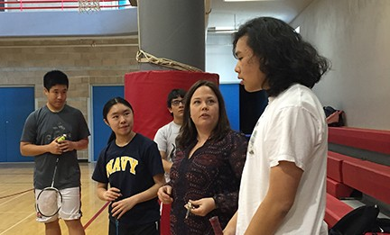 Teammate Sarah Hong and alumnus Shing Hoi Lao listen to badmiton coach Sarah Garlinghouse. The team is currently undefeated in its first four games of the season.