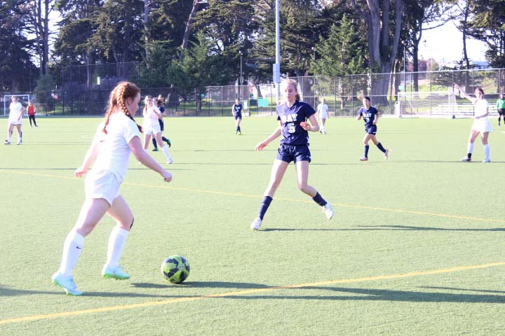 Freshman Cece Giarman prepares to pass around her opponent in a match against The Bay School of San Francisco. The Convent team has players of all grades and skill levels who began their season in February.