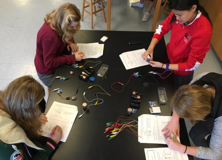 Juniors Lauren Key, Isabella Pontecorvo and April Matsumoto and senior Julia Praeger (bottom left, counter clockwise) complete circuits to detect energy in connecting wires during a physics lab.