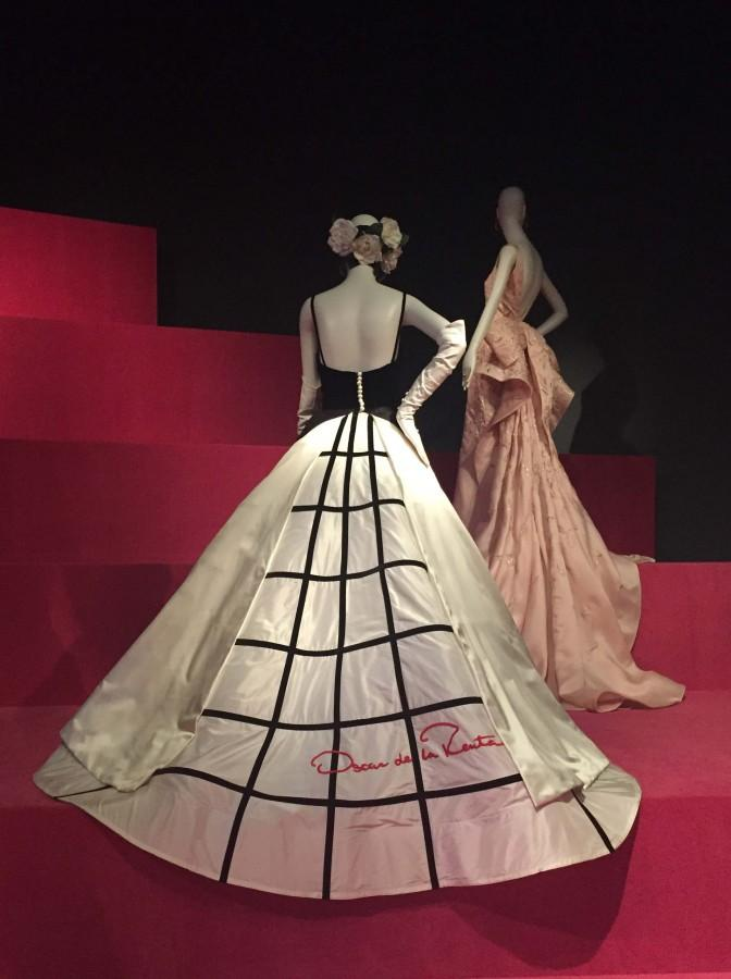 A+custom+evening+dress+made+for+actress+Sarah+Jessica+Parker+is+on+display+at+the+%22Oscar+de+la+Renta%3A+The+Retrospective%22+exhibit+at+the+de+Young+museum.+The+dress+is+made+of+white+duchess+satin+with+black+silk+velvet+and+the+designer%27s+name+embroidered+across+the+back.