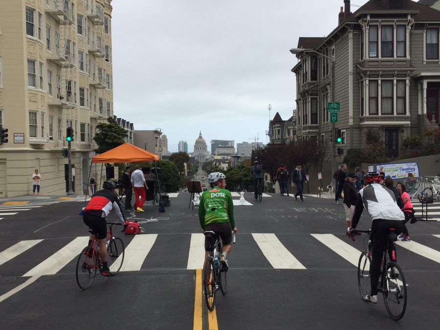 Three bikers ride down Fulton Street, a car-free area of the Western Addition Sunday Streets. The concept of closing streets to vehicles to create outdoor neighborhood markets started in Bogotá, Columbia and has spread to cities spanning around the globe.