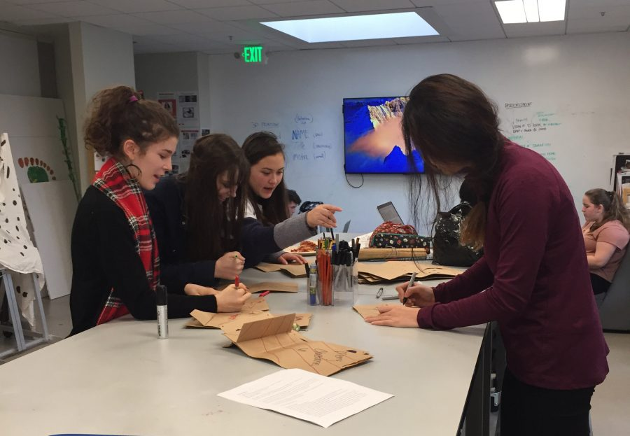 Sophomore Ixchel Boivin, Victoria Berhart and juniors Erika Wong and Sarah Mahnke-Baum, meet in the Art Room during lunch to decorate care packages. Necessities such as socks, underwear, hats, gloves and books were placed in the packages.