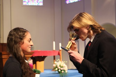 Senior Bella Kearney looks on as sophomore Jack Honeyman drinks from a chalice.  When Catholics elect to receive the cup, it symbolizes sharing the cup that Jesus Christ drank from at the Last Supper.