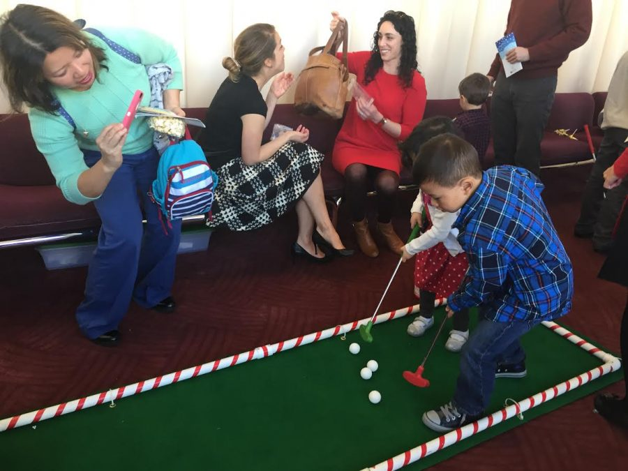 Kids play miniature golf during the annual Deck the Halls event, featuring activities for attendees.