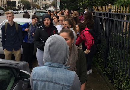 Students stand outside the Italian Consulate after evacuating the campus. Fire alarms first rang from the Siboni building after an incident in the physics lab.