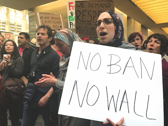 Muslim-American protestor Asmaa Mourad stands with her mother Nihad Mourad repeating a series of chants in the international terminal of San Francisco International Airport. Some protestors made camp in the terminal from the night before and distributed free food, beverages and feminine hygiene products to all attendees.