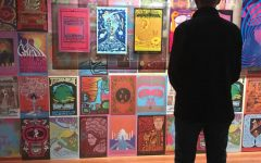 "A de Young Museum visitor views vintage music posters  at ""The Summer of Love Experience: Art, Fashion, and Rock & Roll."
