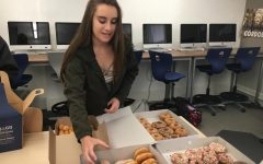 Sophomore Kate Etter reaches for a doughnut during the Computer II class's end of the semester party. The class chatted about their plans for summer during the period.