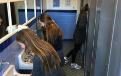 Sophomore Elizabeth Worthington and junior Sinead McKeon wash their hands in the second floor bathroom of the Flood Mansion that was last updated in the 1940s. Antiquated plumbing contributes to frequent clogging of the pipes.