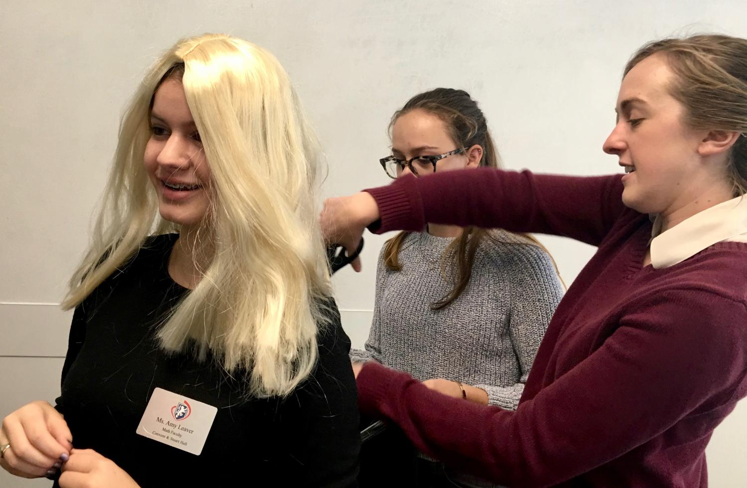 Math teacher Amy Leaver trims junior Olivia Mohun's blonde wig to complete Mohun's Student-Teacher Swap look. Today was the first of the five day Spirit Week, with Decade, Pajama, Jersey and Convent & Stuart Hall Spirit Days as the themes throughout the rest of the week.
