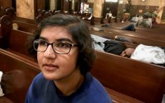Sophomore Arianna Nassiri sits in a pew in front of men taking part in the Gubbio Project at St. Boniface Church. The Gubbio Project worked with St. Boniface to provide a safe and quiet space for homeless people to rest during the day.