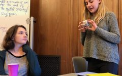 Freshman Lola Morrell listens to Grace Krumplitsch present her self-portrait to her G Period English I class. Many students opted to draw their self-portraits but others made 3-D designs like Krumplitsch's cube.
