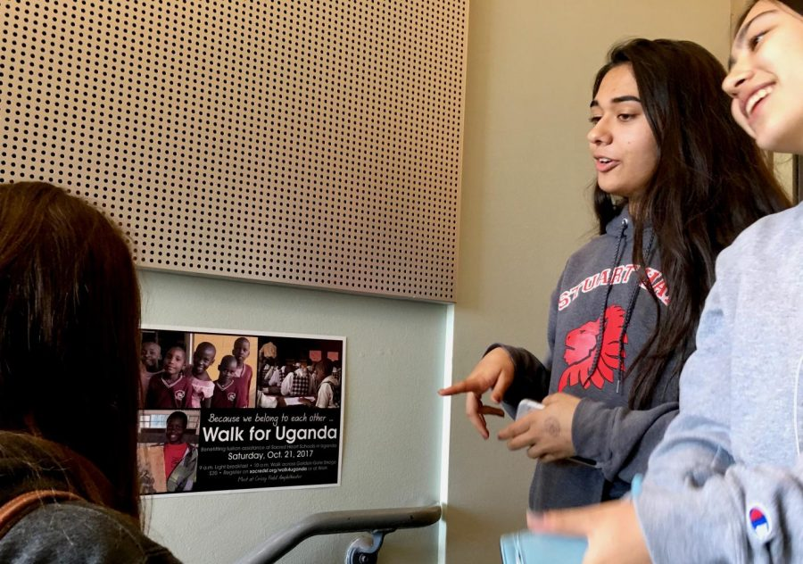 "Sophomores Caroline Thompson, Isabelle Paul and Colette Hom read the Walk for Uganda informational poster and talk about their plans to support the schools in Uganda. These girls, among others, decided to ""Sleep in for Uganda"" and will donate without going to the event."