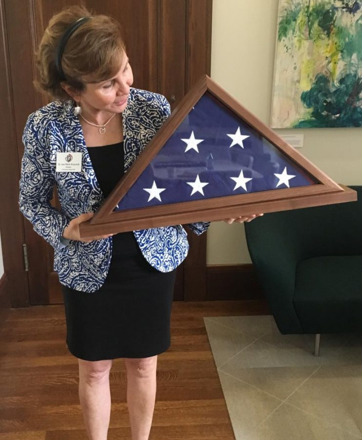 President Ann Marie Krejcarek holds the flag gifted to the school by House Minority Leader Nancy Pelosi. The Capitol Flag program allows members of Congress to request a flag to be flown over the U.S. Capitol on behalf of a constituent.