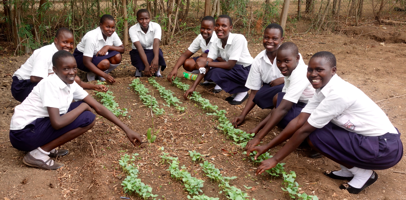 Girls from the agricultural club at Kangole Senior Secondary School pose with the beginnings of their greenhouse project. The club is responsible for maintaining the project, which is one of the efforts that the school has initiated in an effort to become self-sustaining.