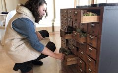 Sophomore Dena Silver looks inside the drawers of the Bardo. The art piece will stay in the Belvedere until the end of the book fair.