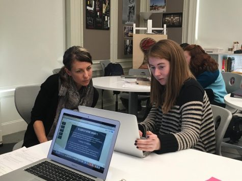 Extended Essay Coordinator Alyson Barrett-Ryan assists junior Sophie Egan with her extended essay. Students's subject areas and initial research questions were due Monday.