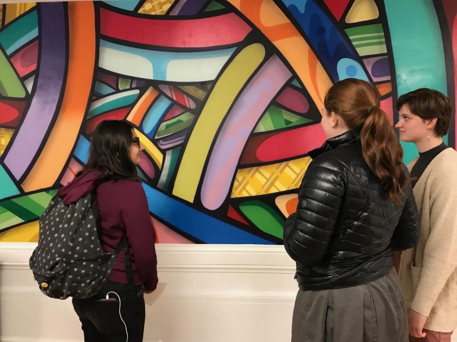 Sophomore Lauren Tulley explains the color choices of the mural to sophomores Cat Webb-Purkis and Sophia Aeby. Tulley worked with two other students to help to coordinate the mural and it's location.