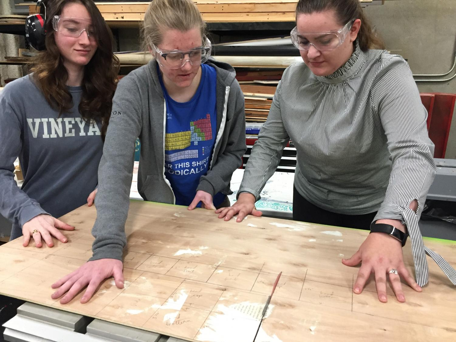 Seniors Natalie Lunbeck, Lizzie Bruce and Francesca Petruzzelli cut a piece of wood to make a robot using a table saw. The robot will serve as the Innobotics Club mascot.
